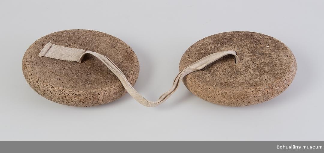 Simdynor av korkplattor, sammanbundna med ett vävt band som är trätt genom korken.