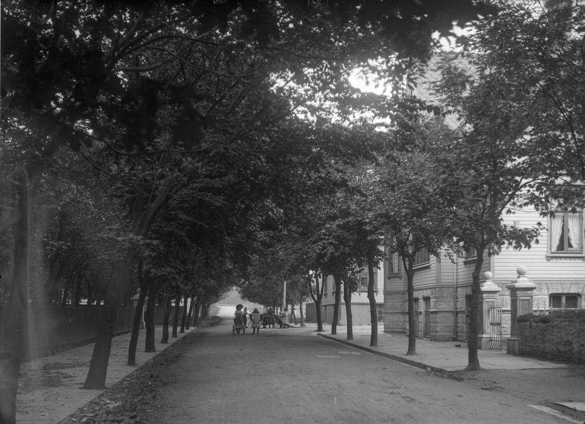 Byparken. Trær til venstre, hovedsaklig trehus til høyre. Barn midt på bildet i gaten, delvis i bakgrunnen.  Fortau på begge sider.