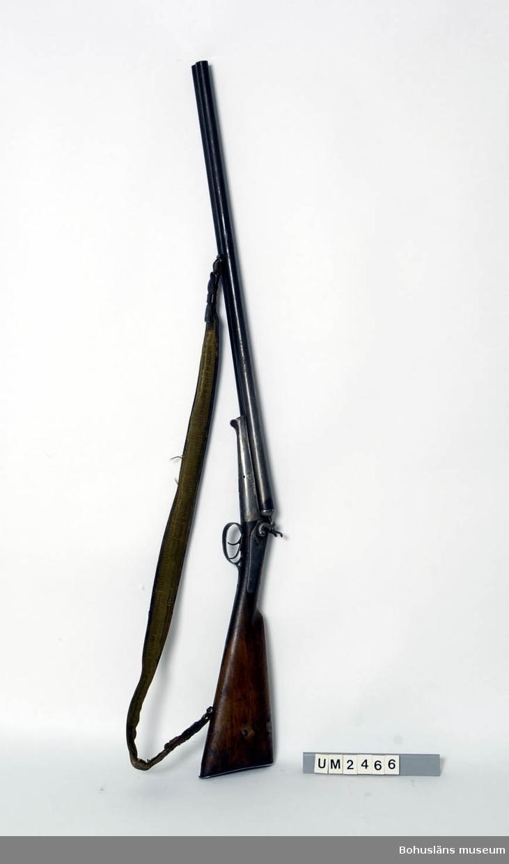 Ur handskrivna katalogen 1957-1958: Tvåpipigt jaktgevär 116 cm längd Tillverkare : Husqvarna vapenfabrik. Träkolv. Axelrem i läder och tyg. Rost på piporna.  Lappkatalog: 55