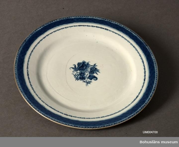 Ur handskrivna katalogen 1957-1958: (Ostind.) tallrik, blå, spräckt Diamet.: c:a 24,8 cm. Vit med blå bård samt blommotiv i mitten. Tunna sprickor i porslinet. Flat.