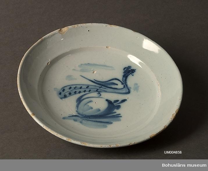 Ur handskrivna katalogen 1957-1958: Tallrik vit m. blå dekor Diam.: 23,2. Smärre skador i kant och glasyr  Lappkatalog: 62