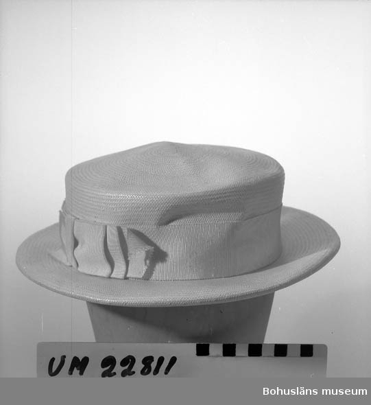 Vit strå, rund kulle, plan översida, vitt ripsband. Rakt, utstående brätte.  Ang. förvärvet och upplysningar om Maria Frankenbergs modehandel i Uddevalla, se UM022807.