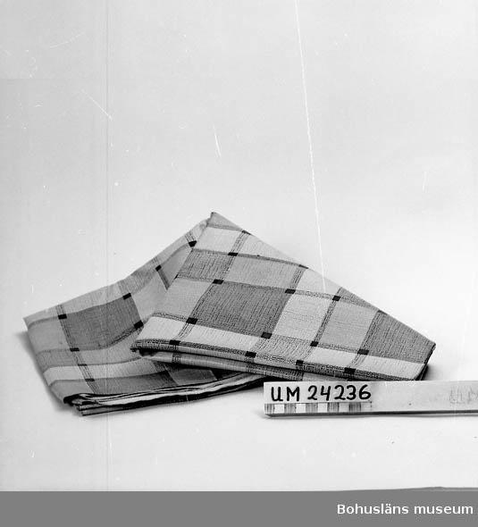 """Tillverkningstid uppskattad. Gul och grårutig. Tillhör campingbordet (UM 24235) men köptes in senare än bordet tillverkades. Text på baksidan duken (tryckt ett flertal gånger): """"textolin, von HORNSCHUCH, mit besonderem Oberflächenschutz gegen verschmutzung. Brukar kallas för vaxduk."""