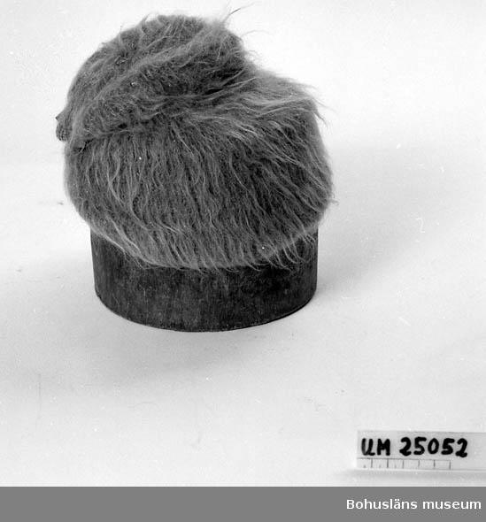 471 Tillverkningstid 1945 CA 594 Landskap BOHUSLÄN  Långfibrigt garn. Uppborstad. Beige. I nacken är det två sycken  röd-gula kuber som dekoration. Givaren född Johansson, 1908, Uddevalla. Hon var tandtekniker och tandsköterska.
