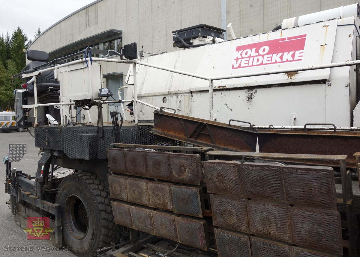 To-akslet asfaltutlegger på fire hjul. Fylletrakt i bakkant og selve utleggeren i framkant. Propantanker og varmeelement for oppvarming av gammel asfalt.