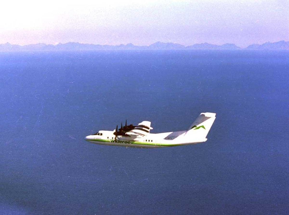 Luftfoto. Et fly, LN-WFK, DHC-7 /Dash7 fra Widerøe på tur over Vestfjorden i Nordland. Lofotfjellene i bakgrunn.