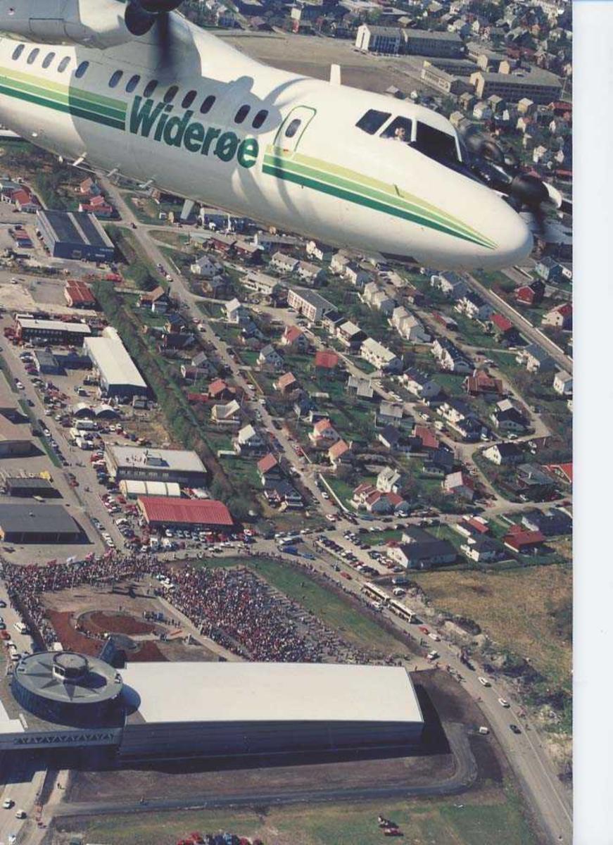 Luftfoto. Et fly, LN-WFI, DHC-7 / Dash7 fra Widerøe, fotografert over Bodø og Luftfartsmuseet i forrbindelse med åpningen av Norsk Luftfartsmuseum Bodø.