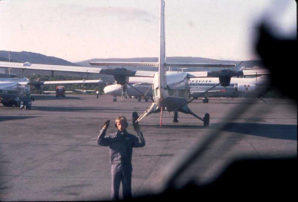 Lufthavn/flyplass. Tromsø/Langnes. En person (marshall) leder et fly til parkeringsplass. Flere fly, både DHC-6-300 Twin Ottere fra Widerøe og DC-9`ere fra SAS parkert på tarmac.