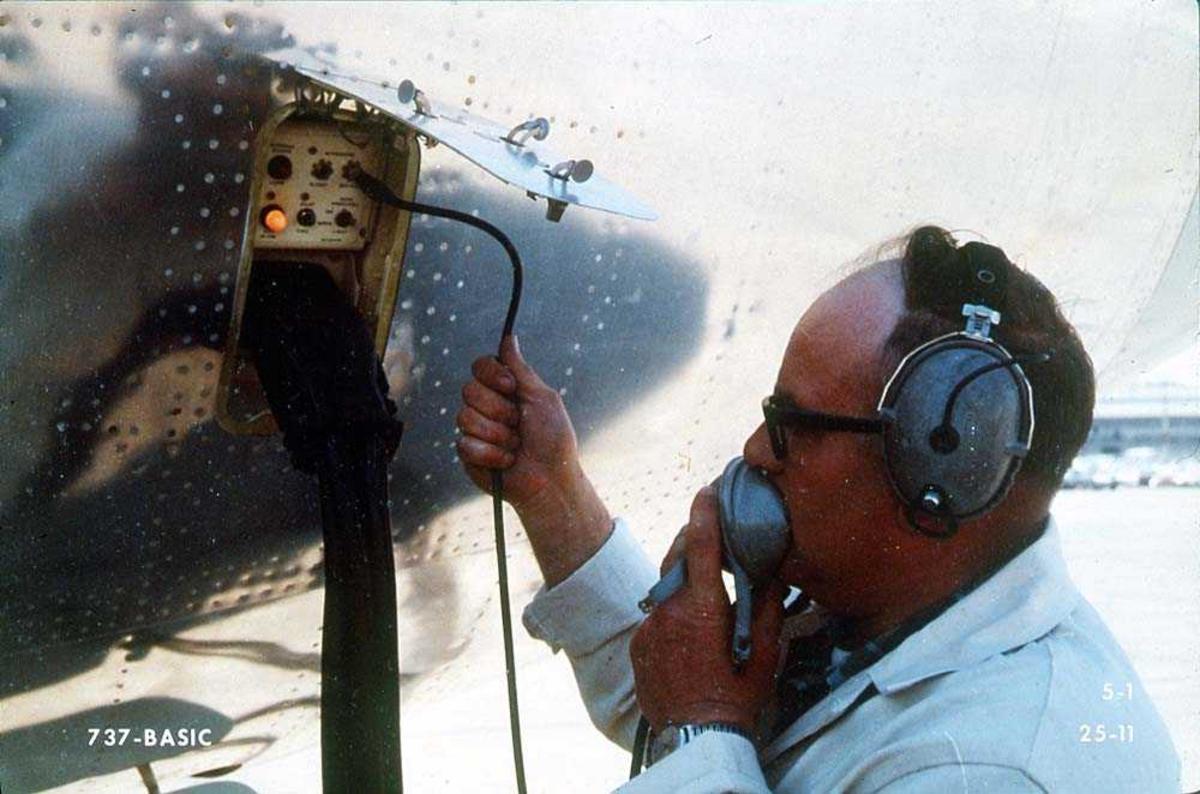 Lufthavn. En person som står med en serviceluke på en Boeing 737, hvor det er tilkoblet to kabler.