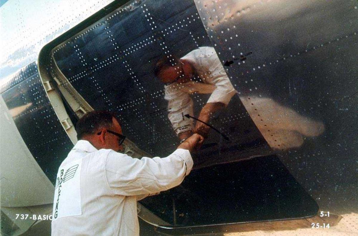 En person som åpner en lasteluke på ett fly, Boeing 737.