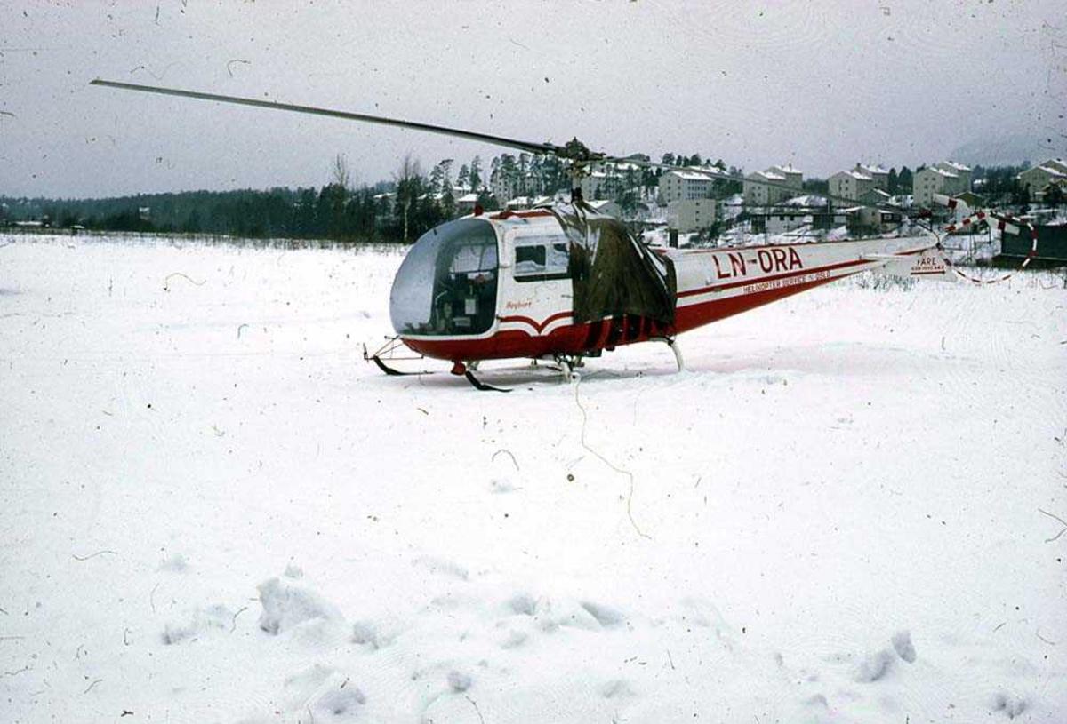 Ett helikopter på bakken, Bell 47 J Ranger LN-ORA fra Helikopter Service. Snø på bakken.