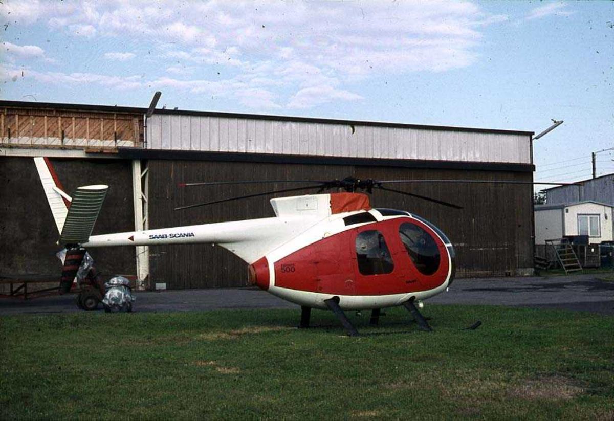 Ett helikopter på bakken, Hughes 500. Bygning i bakgrunnen.