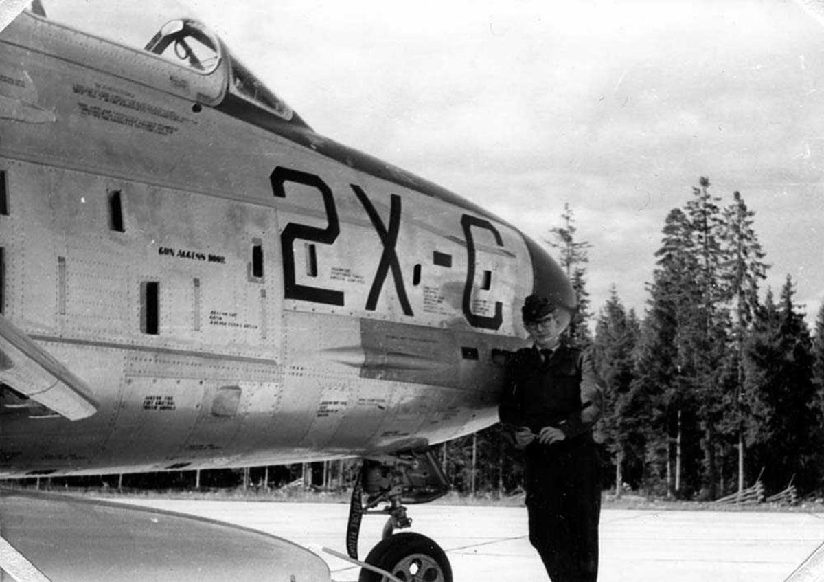 En person i militæruniform som står ved ett fly F-86K.