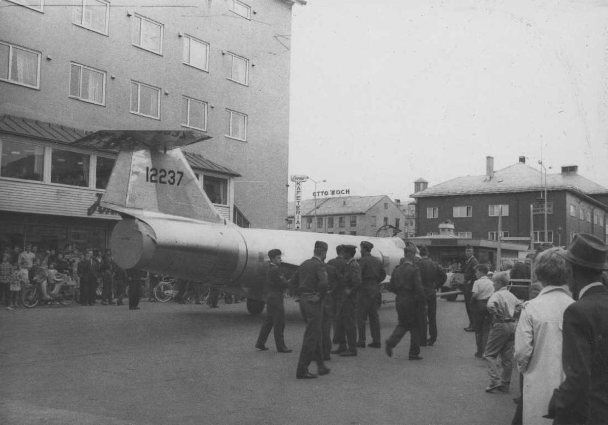Tettsted - By. Ett fly, F-104 Starfighter, transporteres gjennom bygatene. Flere personer står å ser på