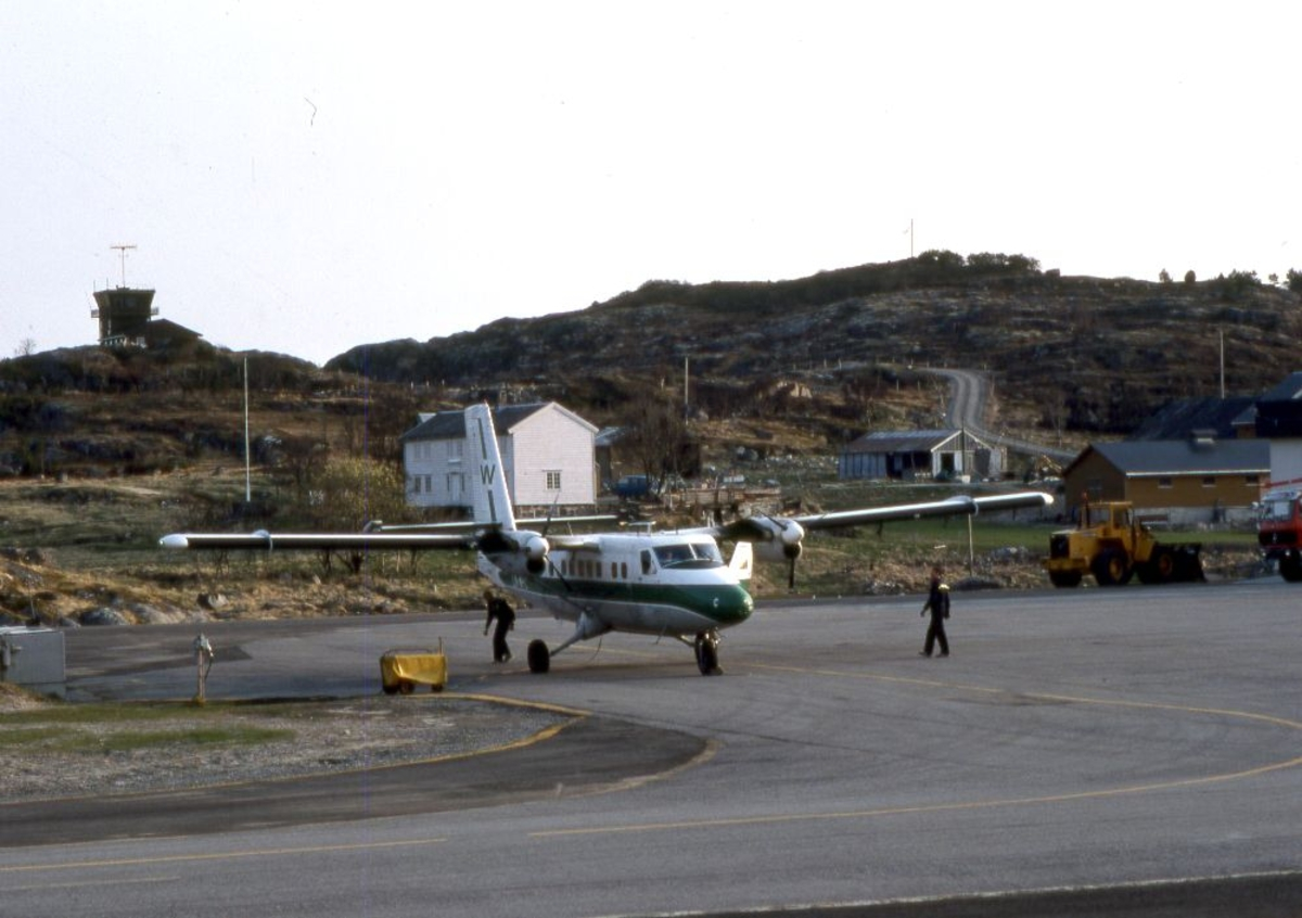 Lufthavn (flyplass). Et fly, LN-WFC, DHC-6-300 Twin Otter fra Widerøe parkert. To personer klargjør flyet for avgang. På en høyde i bakgrunn ligger Flytårnet.