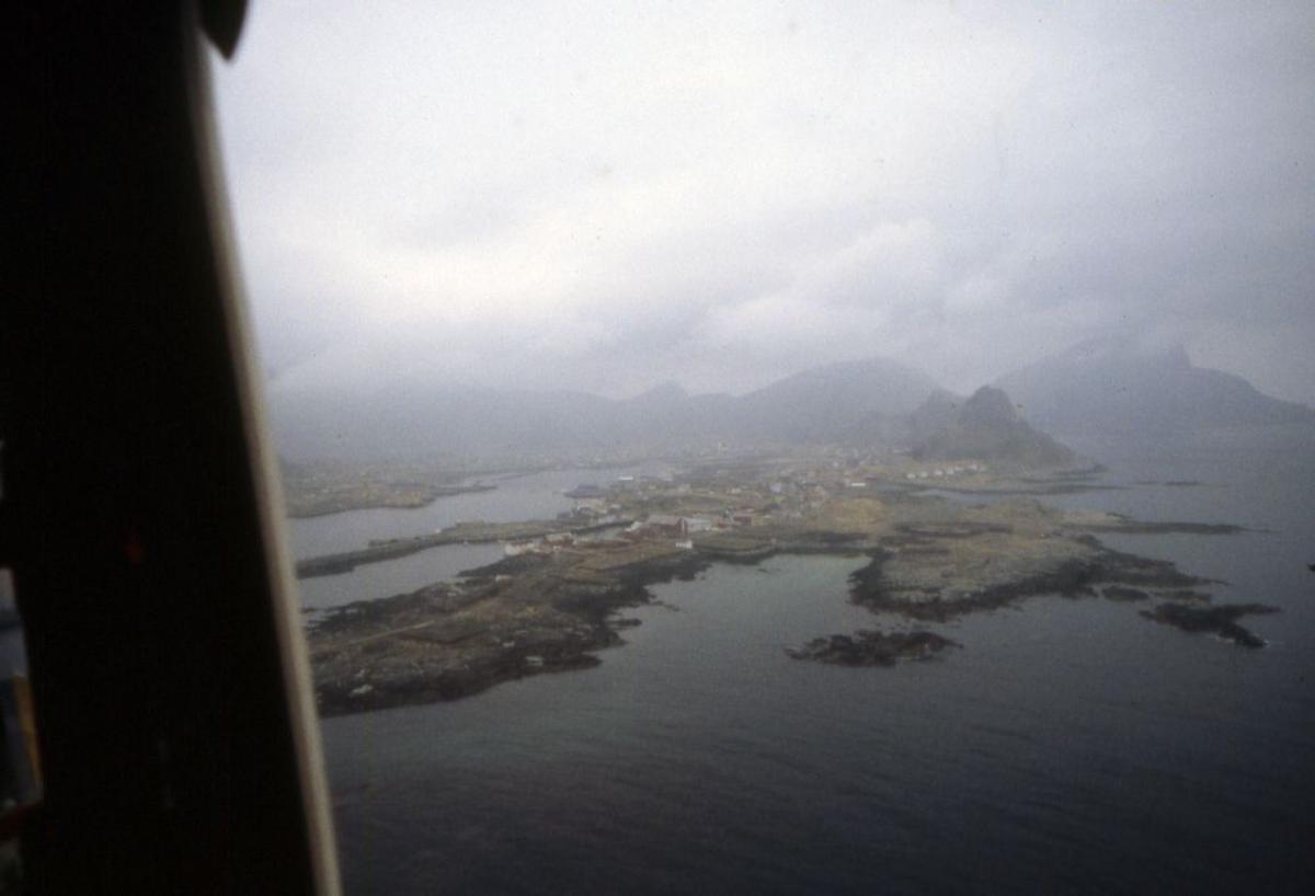 Luftfoto. Et fly,  DHC-6-300 Twin Otter fra Widerøe passerer Værøy.