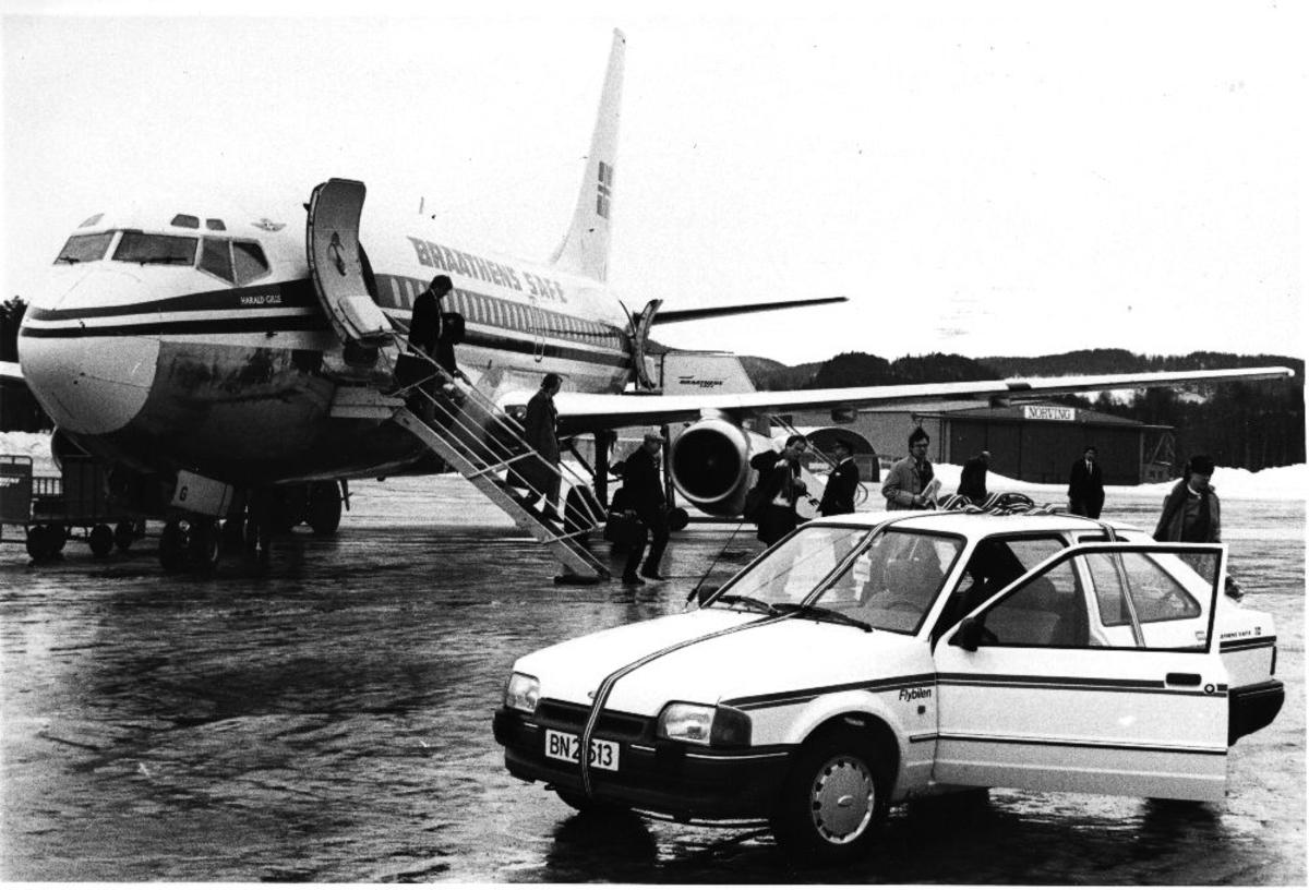 Lufthavn/flyplass. Et fly, LN-SUG, Boeing 737-205 fra Braathens SAFE, har landet og passasjerene forlater flyet. Foran flybilen.