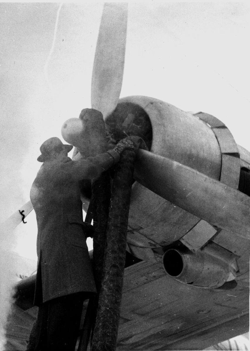 Lufthavn/flyplass. Gardermoen. En person tilrettelegger oppvarming av motor før start, på en DC-4 fra Braathens SAFE.