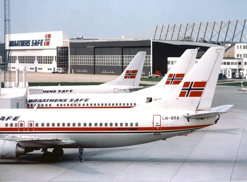 Lufthavn/flyplass.  Tre fly, Boeing 737 fra Braathens SAFE, oppstilt på parkeringsplass (tarmac). I bakgrunn Baathens SAFE's tekniske avdeling.