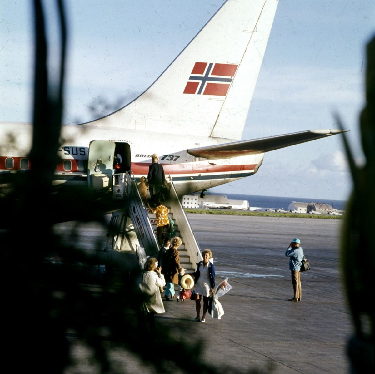 Lufthavn/Flyplass. Et fly, LN-SUS, Boeing 737 fra Braathens SAFE, tar imot påstigende passasjerer.