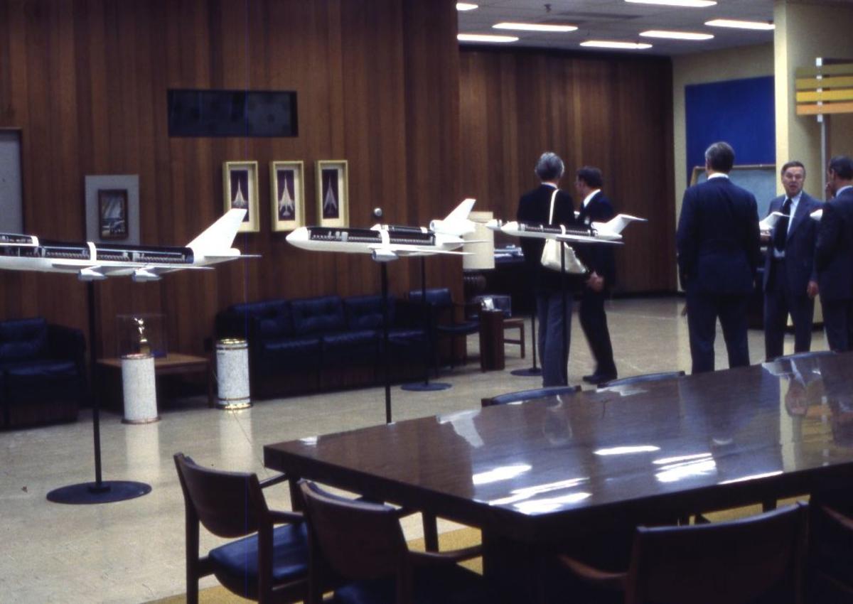 Landskap. Boeings flyfabrikk Seattle. Modeller av flere flytyper er utstilt i et møtelokale. Flere personer tilstede på omvisning.