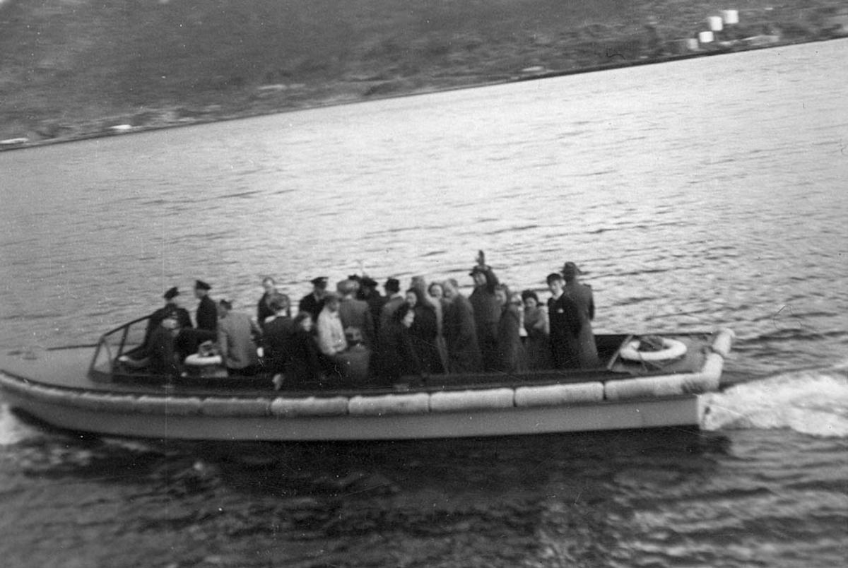 Tilbringerbåt, åpen båt for flypassasjerer. Mange personer ombord.