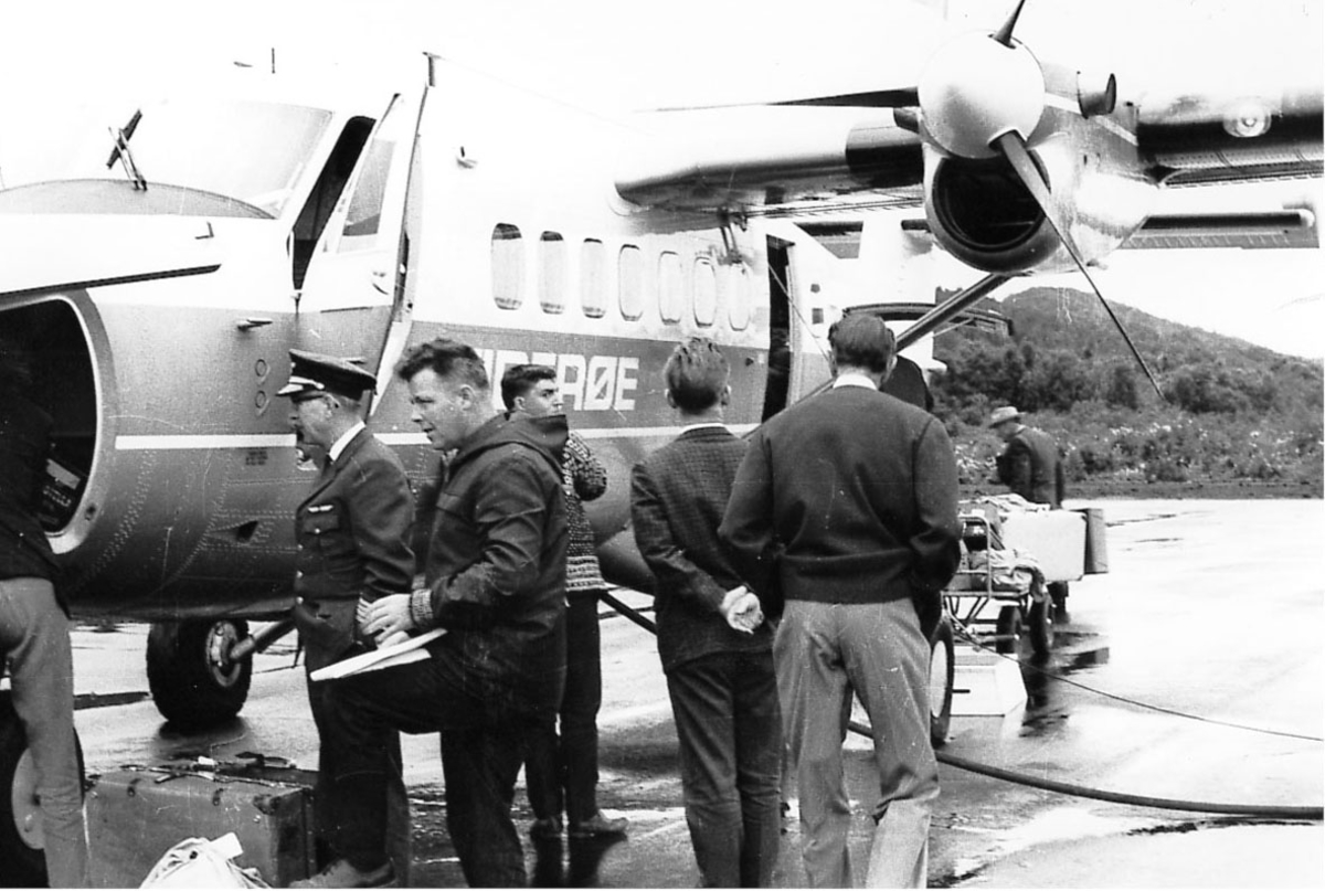 Lufthavn, fem personer foran ett fly, Twin Otter, fra Widerøe. en person og en baggasjevogn i bakgrunnen.