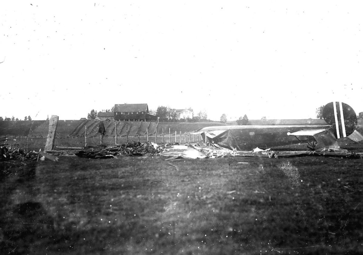 Flyvrak/flykrasj. Avro 504 nr. 107, ligger i mange biter på bakken etter havari. ett gårdsbruk bak.