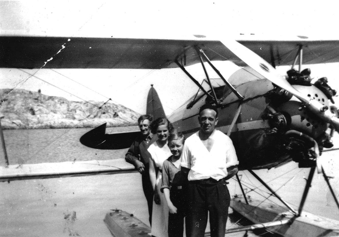Sjøflyhavn, tre personer foran ett fly på vannet,Waco RNF  fra Widerøe.