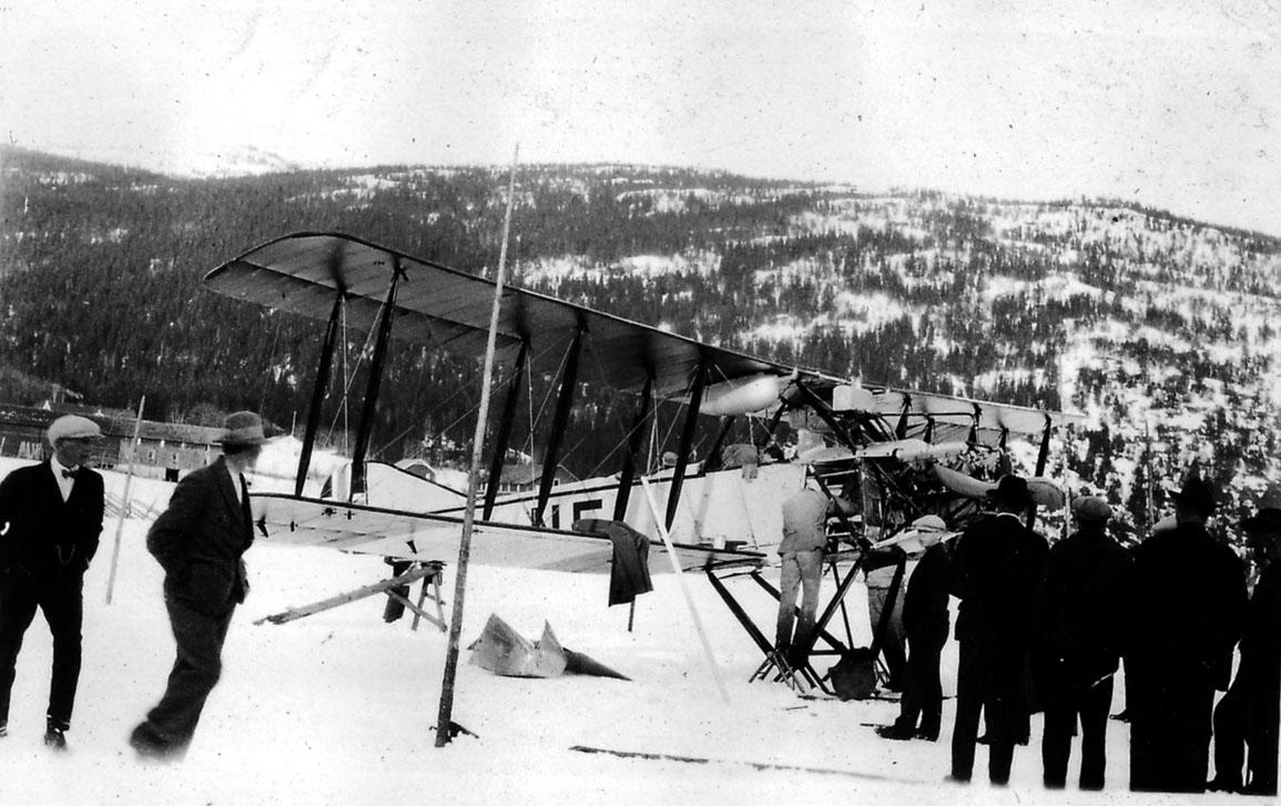 Åpen plass, flere personer ved ett fly på bakken, N5 Avro 501 A (503), med skiunderstell. Ås i bakgrunnen. Snø på bakken.