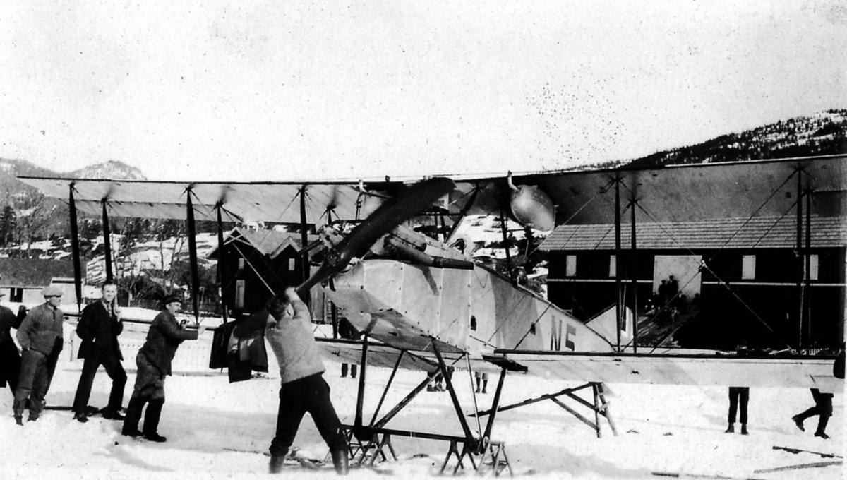 Åpen plass, flere personer ved ett fly på bakken, N5 Avro 501 A (503), med skiunderstell. Bygninger bak, snø på bakken. en person drar i propellen.