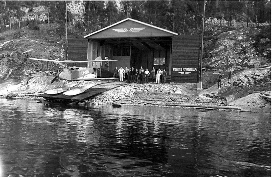 """Sjøflyhavn, Ingierstrand.  Ett fly , De Havilland DH.60 Moth, LN-ABU fra Widerøe ved vannkanten. Hangar bak med påskrift """"Widerøes Flyveselskap"""". Flere personer inne i hangaren."""