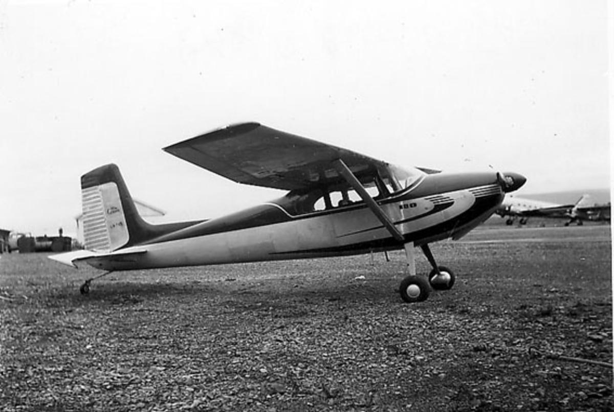 Lufthavn, Ett fly på bakken, LN-TVS, Cessna 180. Ett større propellfly i bakgrunnen.