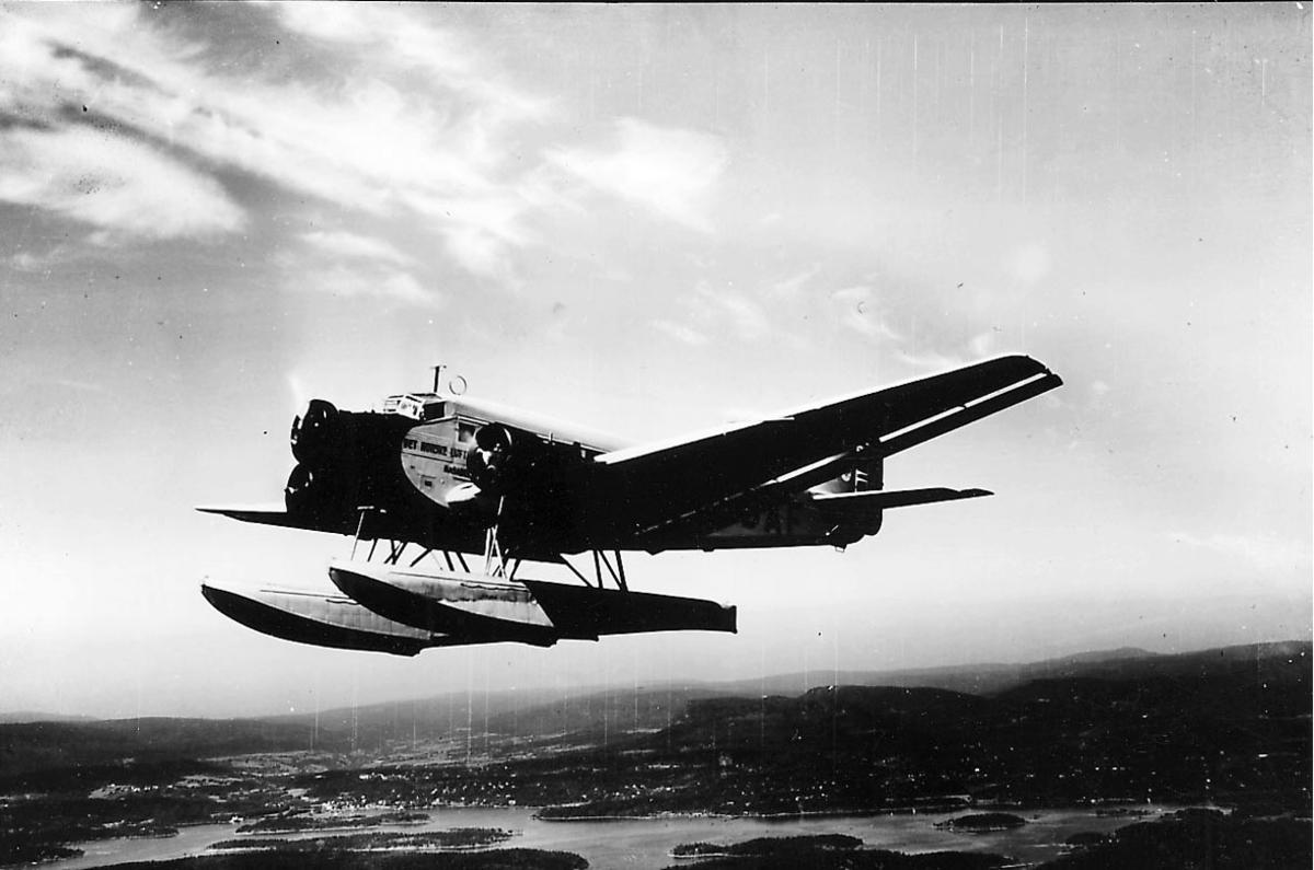 """Luftfoto, Ett fly i luften, LN-DAF. DNL. """"Najaden"""" Junkers Ju 52/3mge.  Landskap med bebyggelse under."""