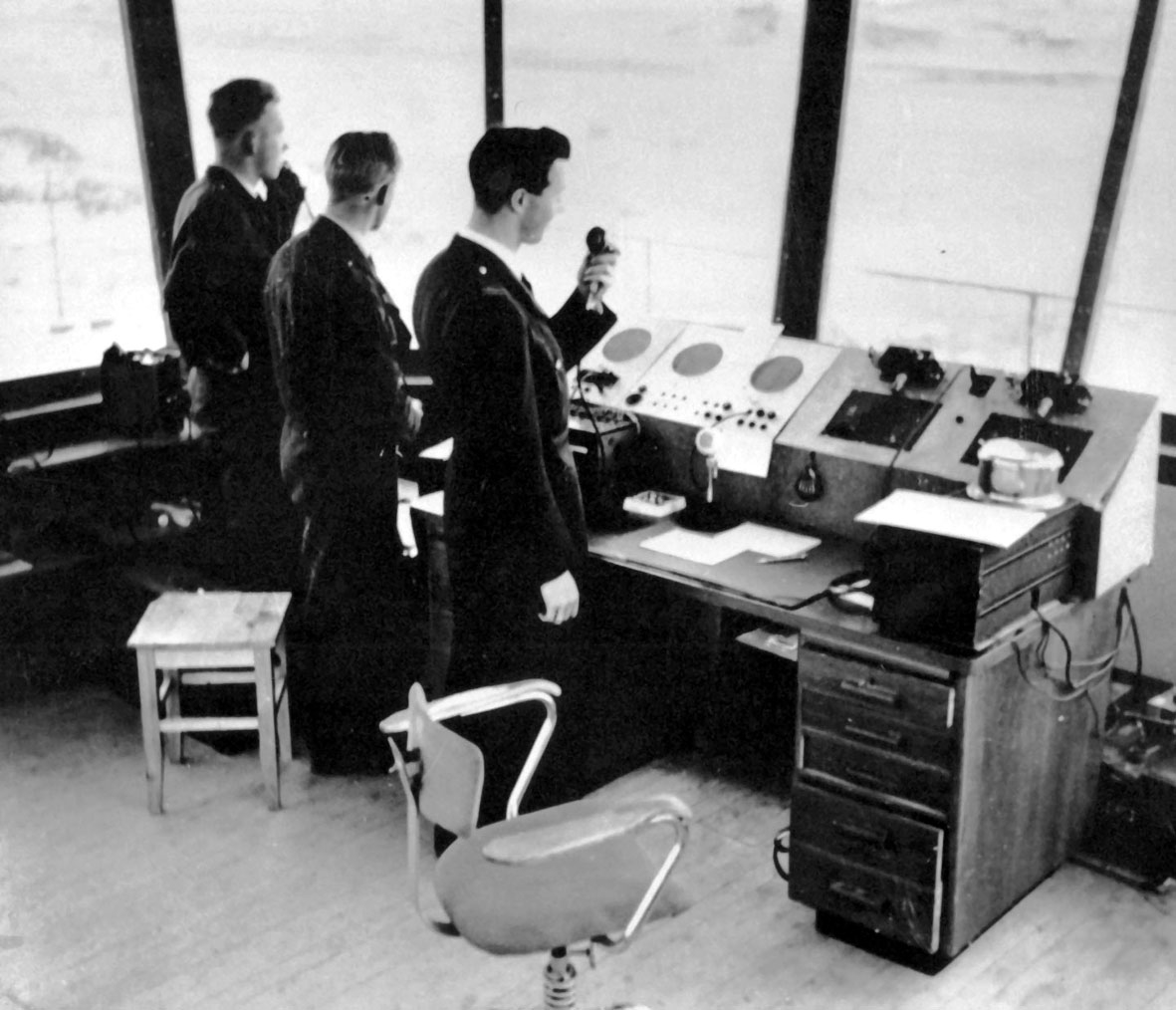 Bodø lufthavn. Portrett, tre personer, en flygeleder, en militær liaison offiser og en flygelederassistent, ved kontrollpulten i det gamle flytårnet. (1952).