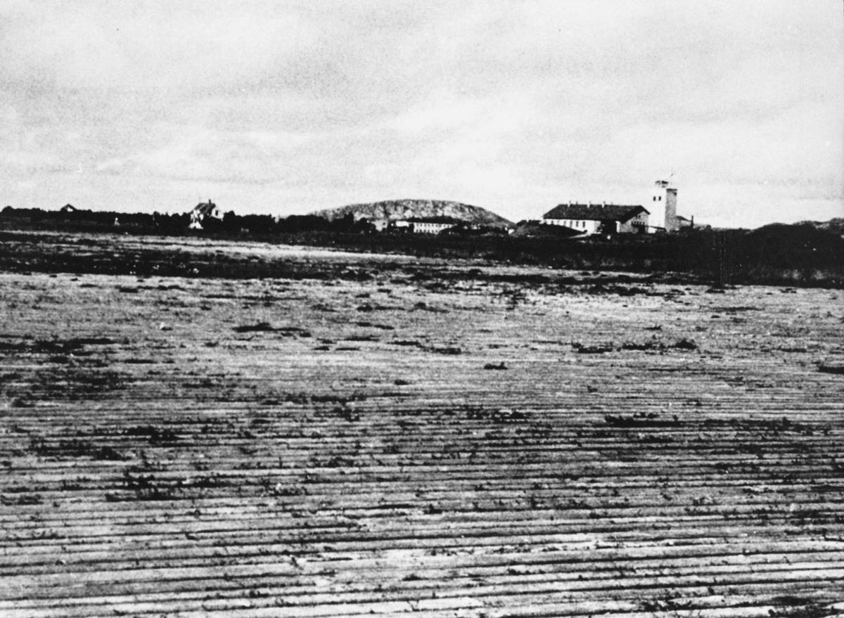 """Bodøs første flyplass, """"plankeflyplassen"""". Noen bygninger i bakgrunnen, bl.a. brannstasjonen til høyre."""