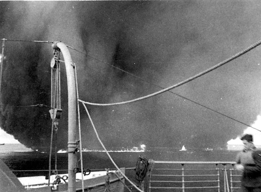 Flere fartøy på åpent hav. Stor røyksky satiger opp, ant. etter bombeangrep. Bildet tatt fra annet fartøy, hvor en person i militæruniform og redningsvest sees t.h.
