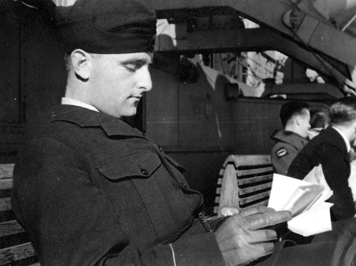 Portrett, noen personer i militæruniform sitter på en benkerad, ant. ombord i fartøy.