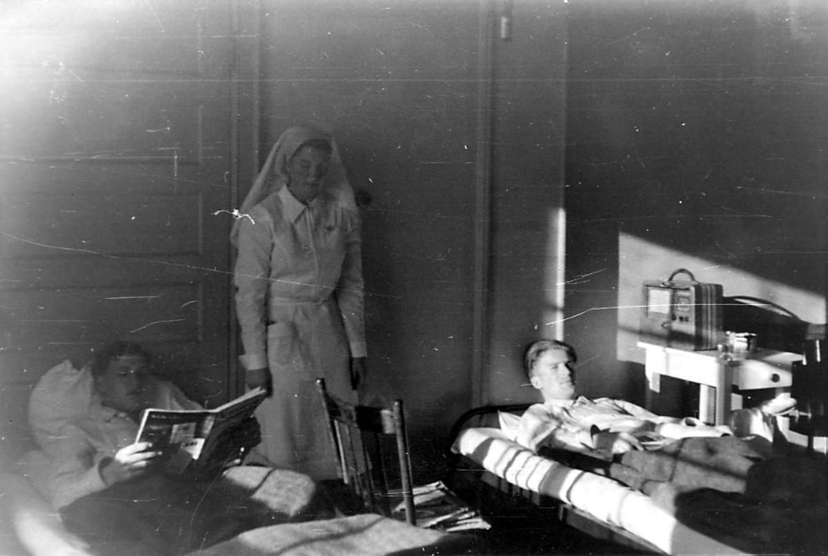 Portrett, tre personer hvor to er mannspersoner som ligger i senger, ant. sykesenger. I midten står en sykesøster..