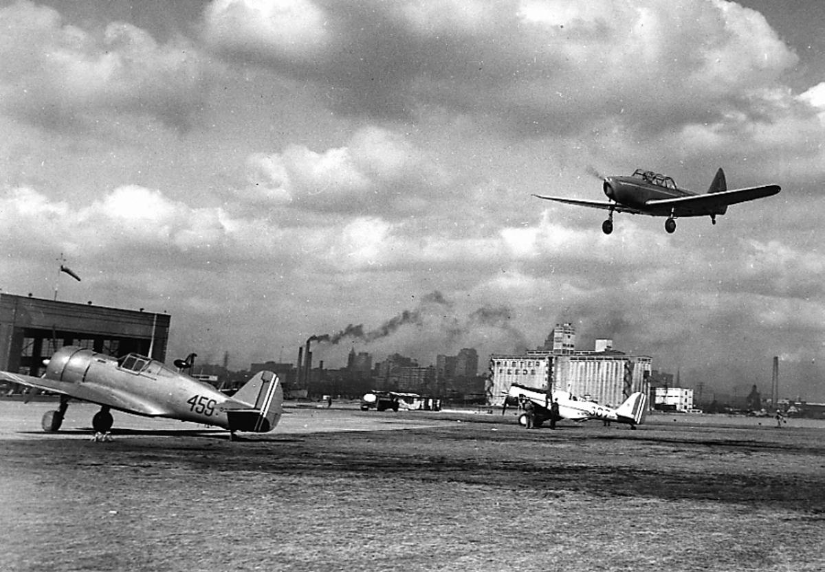 Åpen plass, ant. lufthavn. Noen fly på bakken, et fly like over bakken. Bygninger i bakgrunnen, ant. by.