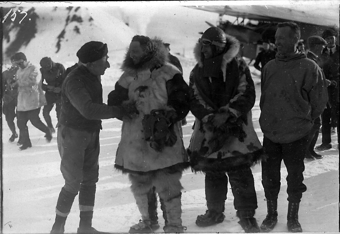 """En gruppe personer, tatt utendørs. Litt av fly bak t.h., Fokker FVII """"Josephine Ford"""". Snø på bakken."""