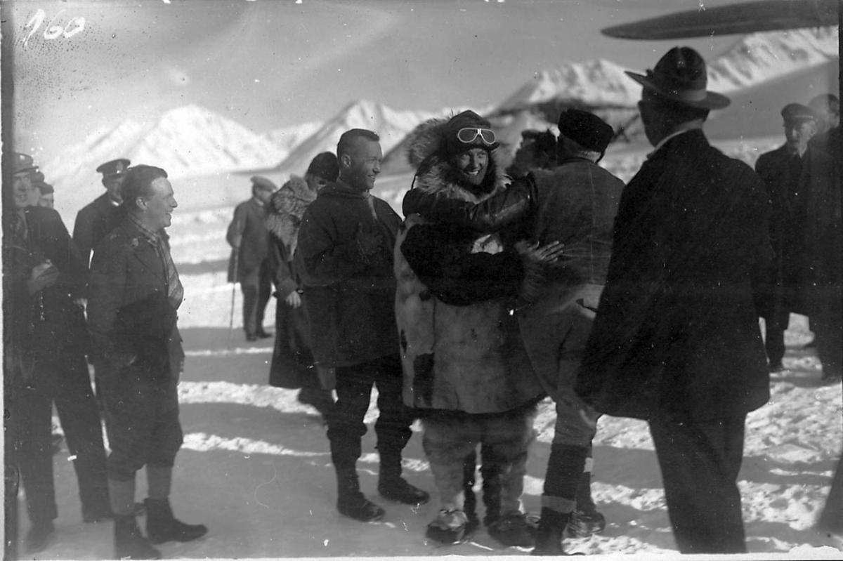 """En gruppe personer, tatt utendørs. Litt av fly t.h., Fokker FVII """"Josephine Ford"""". Snø på bakken."""