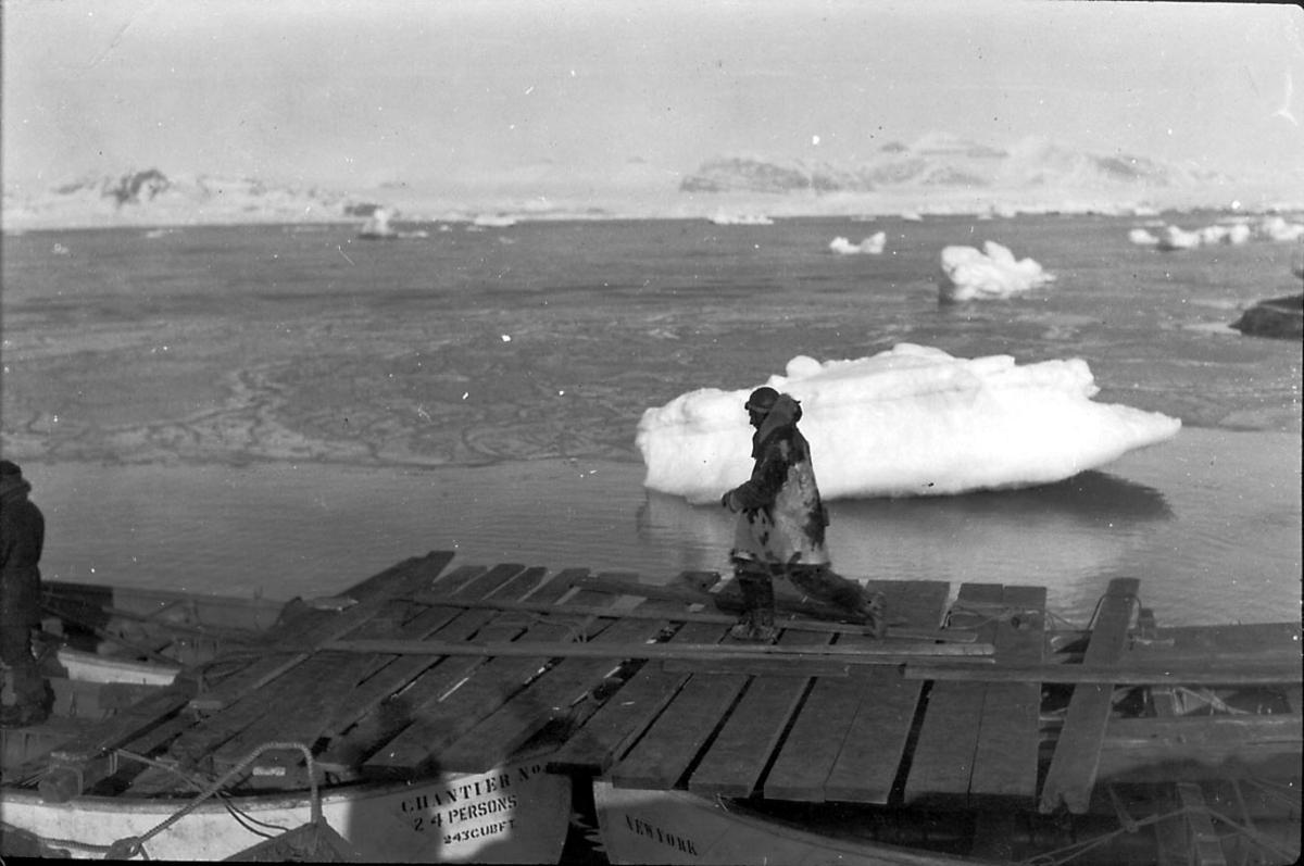 """En person på """"provisorisk """" kai. Mindre isflak i bakgrunnen, hav og fjell."""