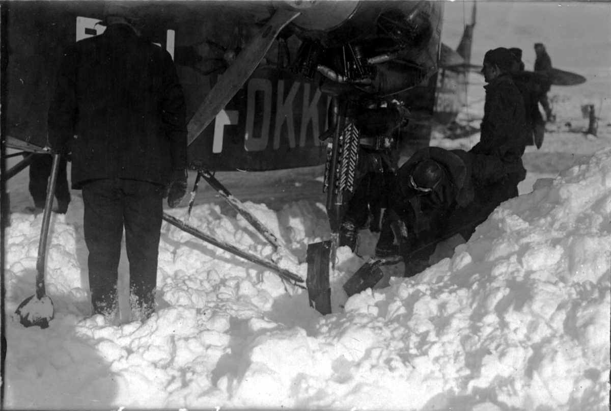 """Fly, propellfly, på bakken, Fokker FVII """"Josephine Ford"""". Flere personer, noen med spader, måker snø ved flyet."""