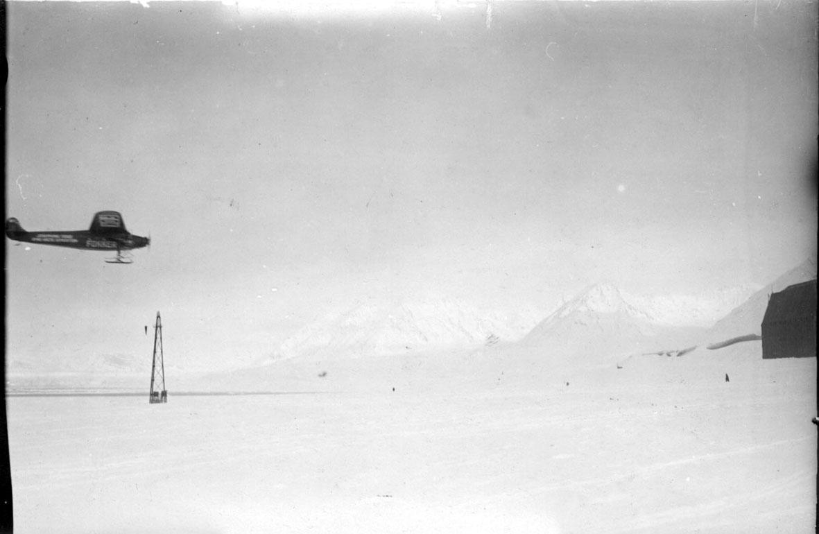 """Fly, propellfly, inn for landing, Fokker FVII """"Josephine Ford"""". Hangaren til Luftskipet """"Norge"""" sees i høyre billedkant, med fortøyningsmasten bak t.v."""