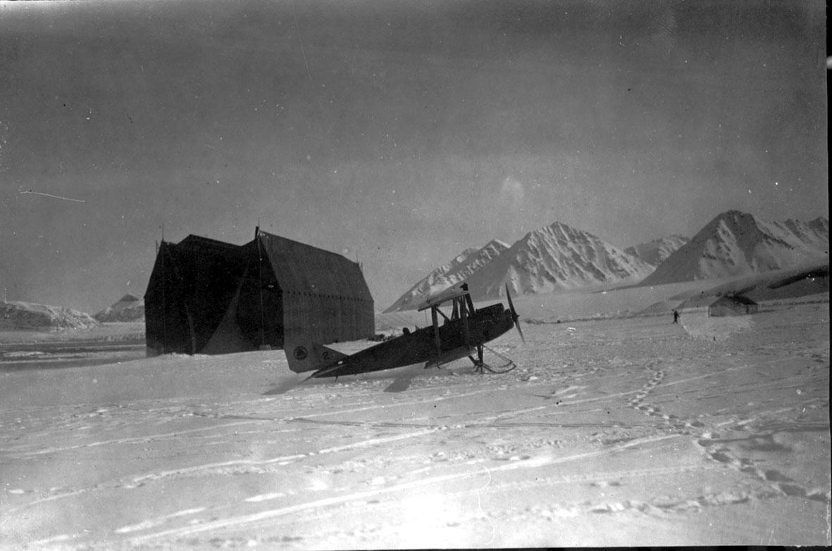 Fly, Curtiss Oriole, i forgrunnen. Luftskiphangaren bak. Snø på bakken.