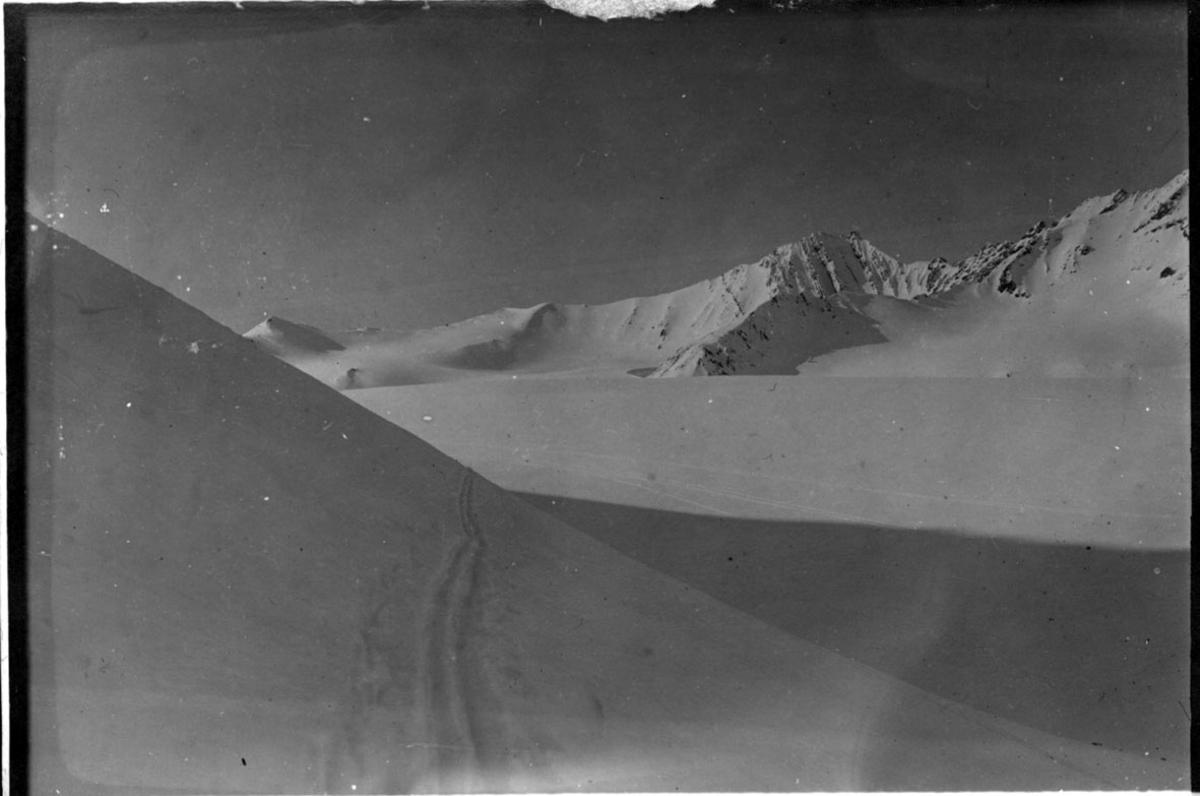 Fra Svalbard, landskapsbilde med snø, fjell og lite dalsøkk. Skispor i forgrunnen.
