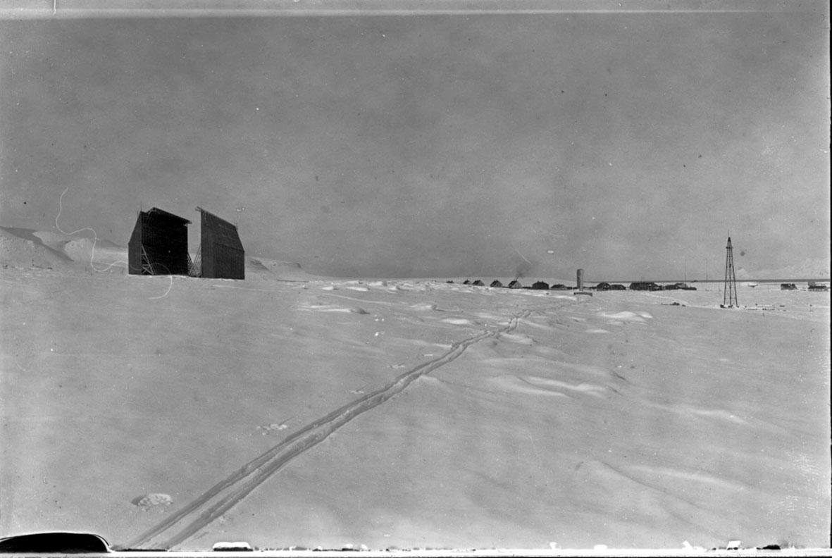 Luftskipshangaren t.v., fortøyningsmast t.h. Flere bygninger, husklynge, i bakgrunnen. Skispor i forgrunnen, snø på bakken.