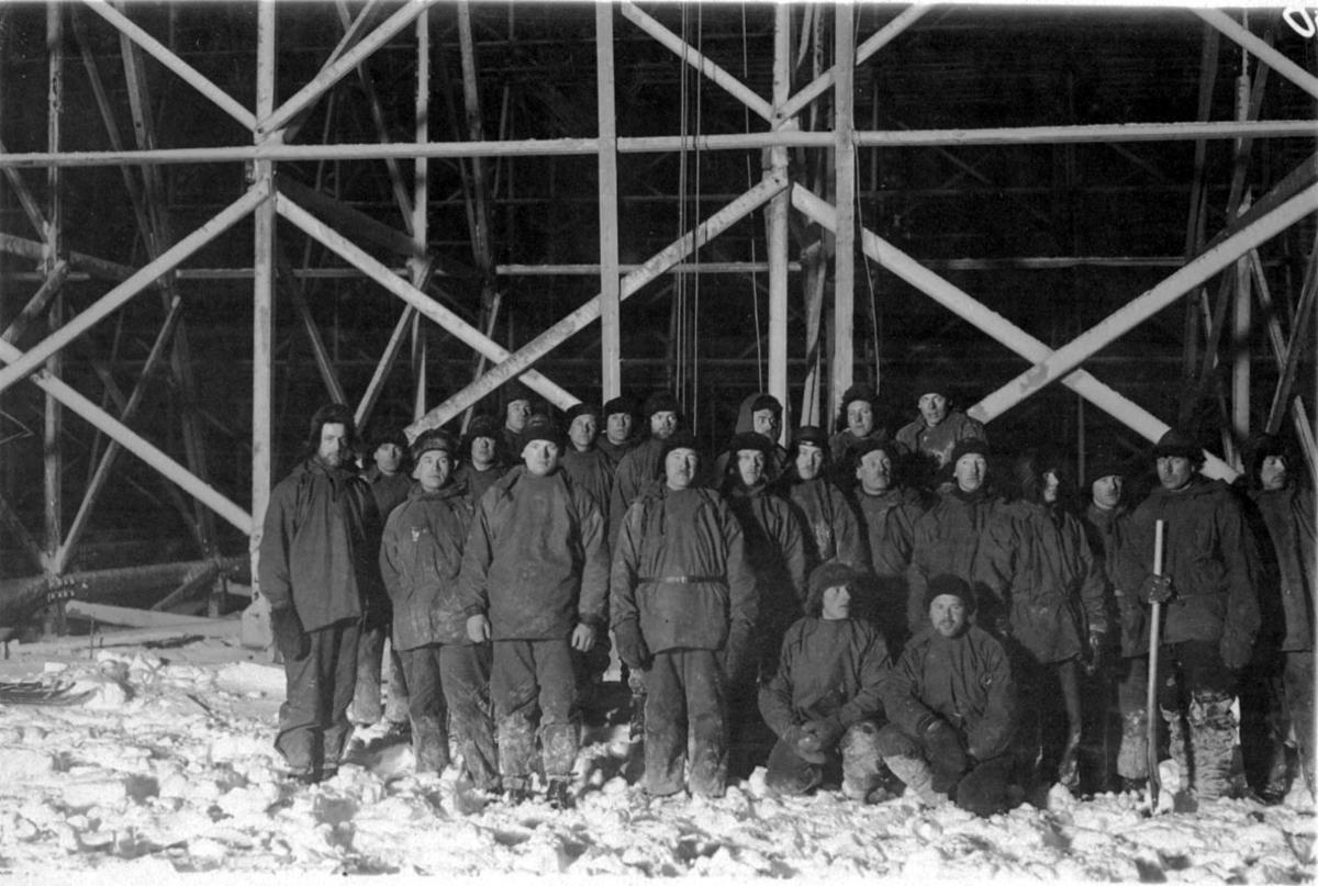 Flere personer oppstilt inne i lufskipshangaren, arbeidslaget. Hangaren er ferdig, men ikke tømt for snø.