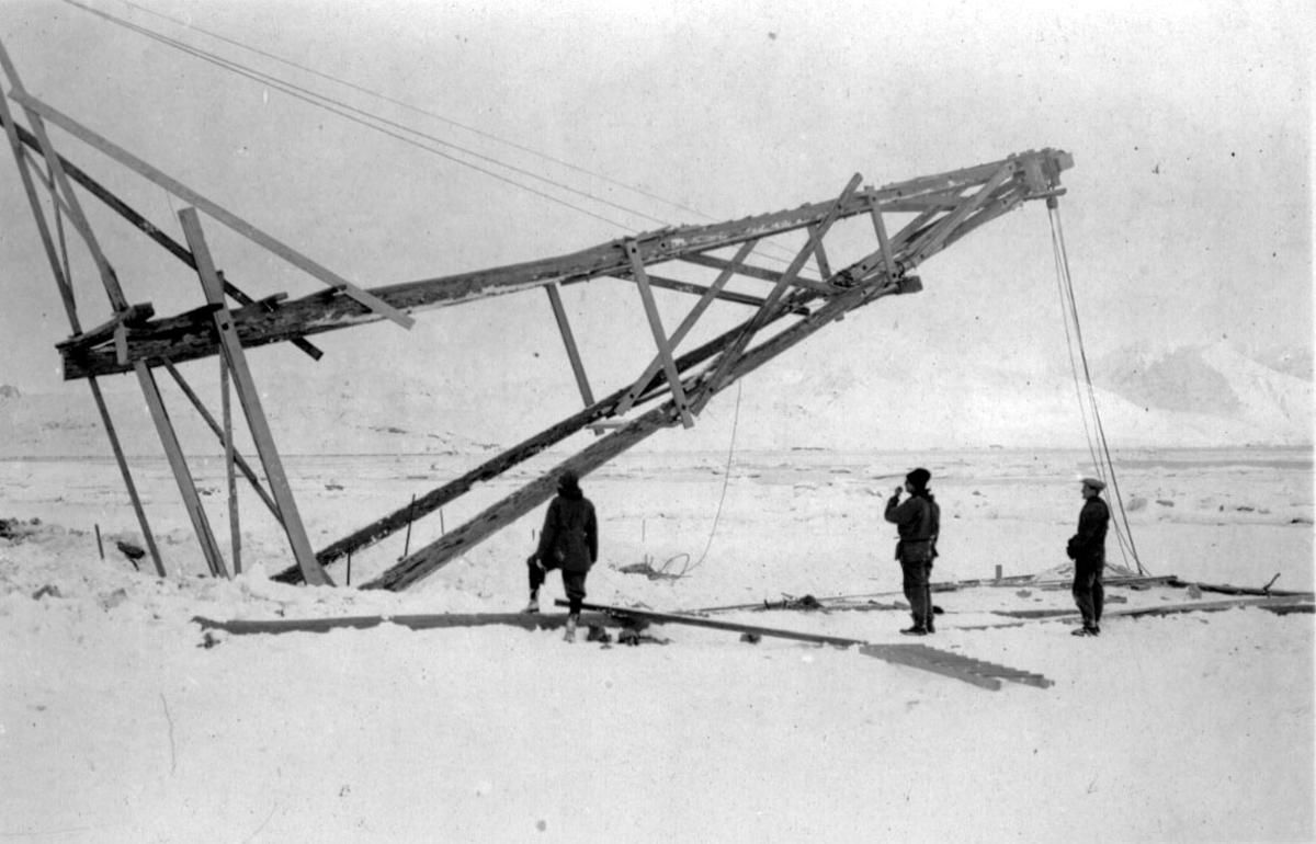 """Løftebukk for fortøyningsmasten til luftskipet """"Norge"""", heises på plass. 3 personer i arbeid. Snø på bakken."""